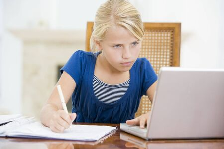 computer writing: Young girl with laptop doing homework in dining room