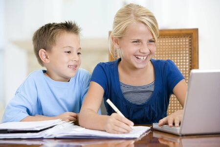 Two young children with laptop doing homework in dining room smiling photo