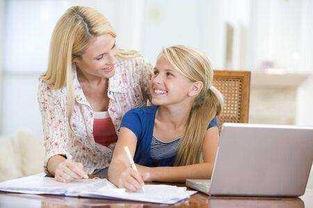 deberes: Mujer ayudando a ni�a con laptop hacer deberes en comedor