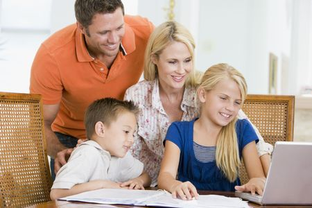 Couple helping two young children with laptop do homework in dining room Stock Photo - 3603445
