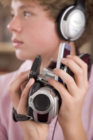 Young boy wearing headphones in bedroom holding many electronic devices photo