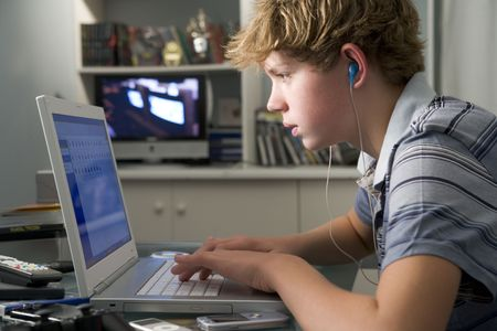 personal computers: Young boy in bedroom using laptop and listening to MP3 player