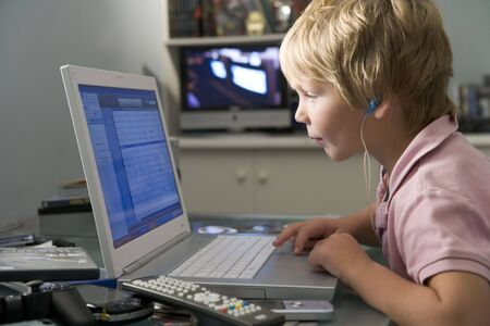 Young boy in bedroom using laptop and listening to MP3 player photo