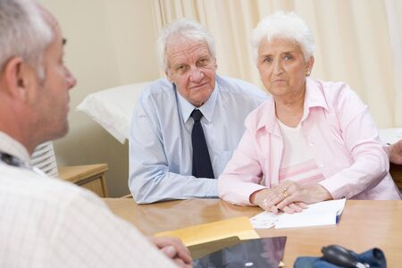 concerned: Couple in doctors office frowning Stock Photo