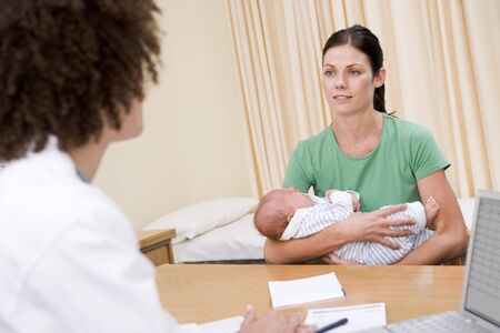 midwife: Doctor with laptop and woman in doctors office holding baby