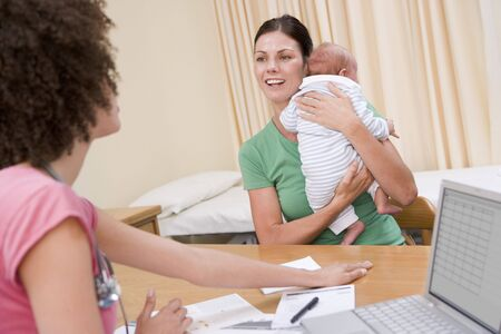 Doctor with laptop and woman in doctors office holding baby photo