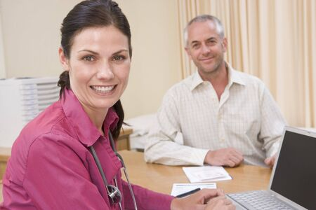 Doctor with laptop and man in doctors office smiling photo