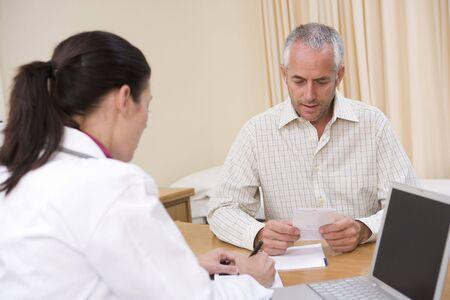 consulta m�dica: Doctor ordenador port�til y con el hombre en el m�dico  's de oficina