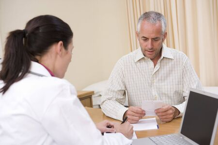 Doctor with laptop and man in doctor's office Stock Photo - 3600905