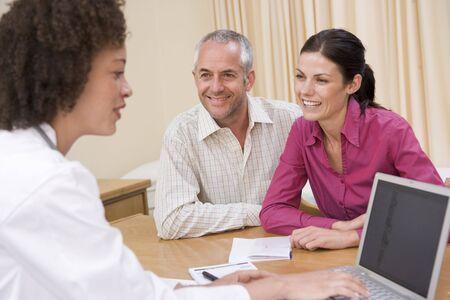 Docteur avec un ordinateur portable et le couple dans le cabinet du médecin souriant Banque d'images