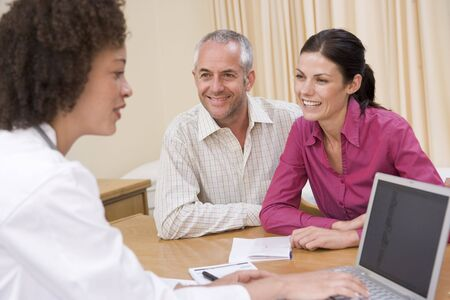 Doctor with laptop and couple in doctors office smiling photo
