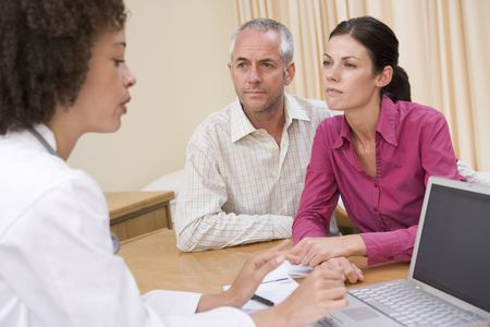 appointment: Doctor with laptop and couple in doctors office frowning