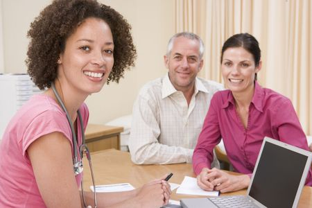 medical physician: Doctor with laptop and couple in doctors office smiling