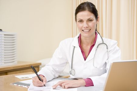 Doctor with laptop writing in doctors office smiling photo