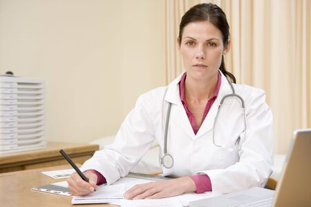Doctor with laptop writing in doctors office photo