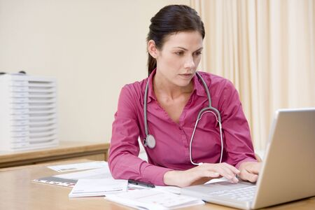 Doctor using laptop in doctors office photo