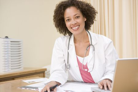 consultant physicians: Doctor with laptop in doctors office smiling