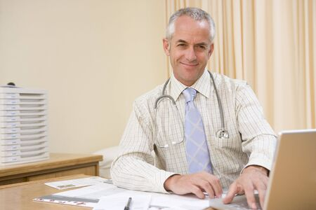 Doctor using laptop in doctors office smiling photo