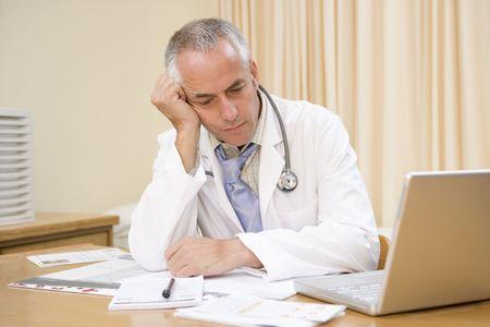 agotado: Doctor con laptop en la oficina del doctor