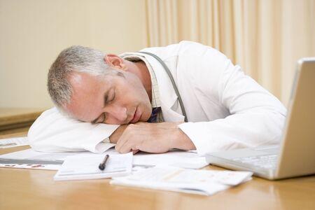 epuise: Docteur ordinateur portable avec de dormir dans le bureau du m�decin Banque d'images