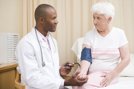 oap: Doctor checking womans blood pressure in exam room Stock Photo