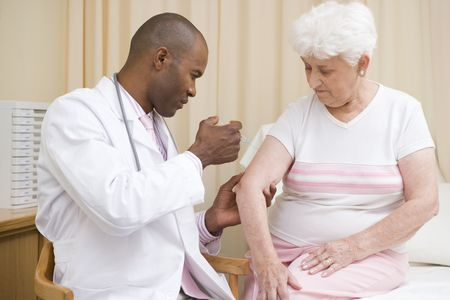 jab: Doctor giving needle to woman in exam room