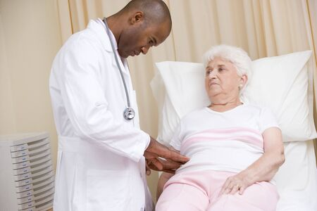 oap: Doctor giving checkup to woman in exam room Stock Photo