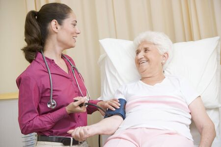 oap: Doctor checking womans blood pressure in exam room smiling Stock Photo