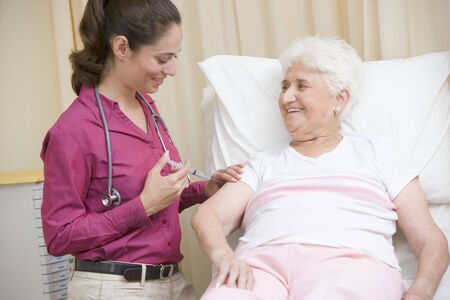 oap: Doctor giving needle to woman in exam room smiling