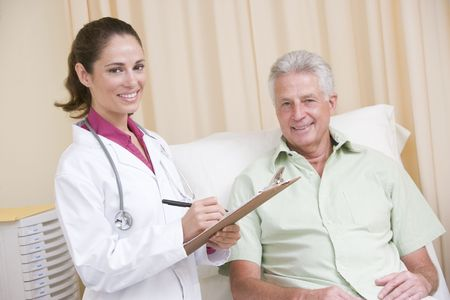 Doctor writing on clipboard while giving checkup to man in exam room smiling Stock Photo - 3600752