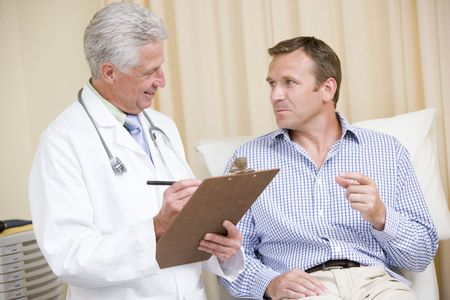 Doctor writing on clipboard while giving man checkup in exam room photo