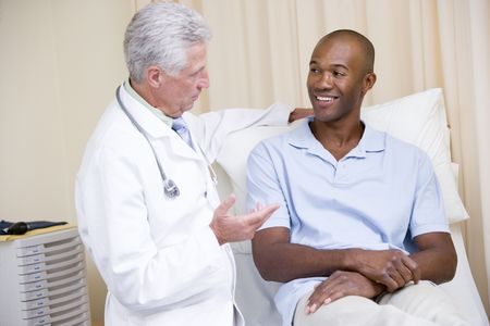 Doctor giving smiling man checkup in exam room photo