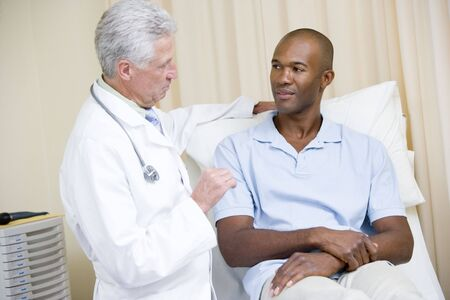 consultant physicians: Doctor giving man checkup in exam room