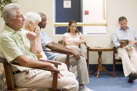 Fünf Menschen warten im Wartezimmer