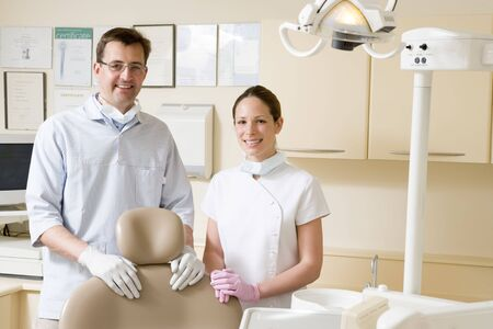 male dentist: Dentist and assistant in exam room smiling