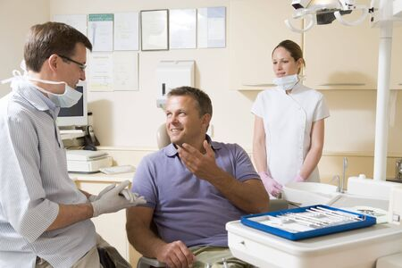 dentist mask: Dentist and assistant in exam room with man in chair smiling