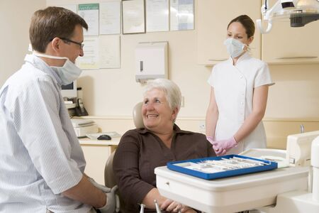 Dentist and assistant in exam room with woman in chair smiling photo