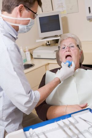 Dentist in exam room with woman in chair photo