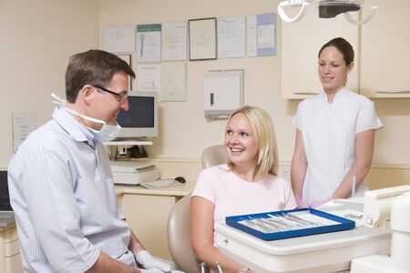 male dentist: Dentist and assistant in exam room with woman in chair smiling Stock Photo