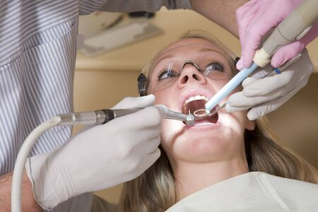 Dentist and assistant in exam room with woman in chair photo