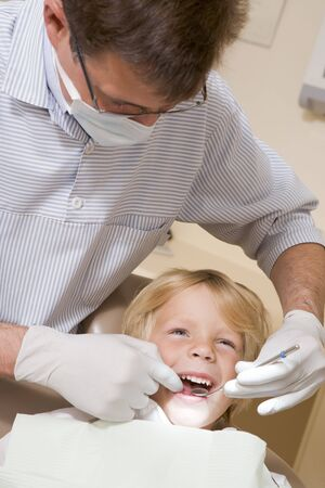 Dentist in exam room with young boy in chair photo