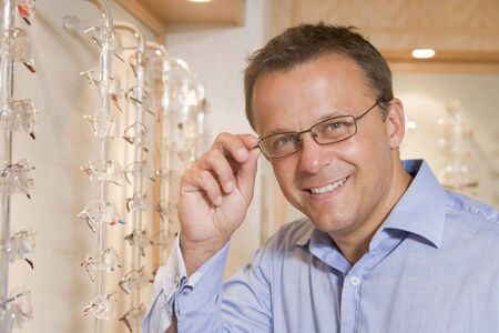 Man trying on eyeglasses at optometrists smiling Stock Photo - 3485295