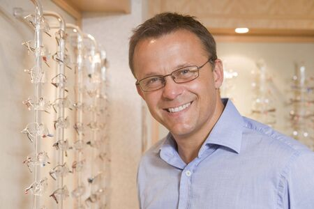 Man trying on eyeglasses at optometrists smiling photo