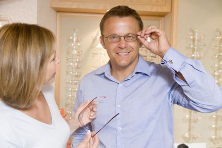Couple trying on eyeglasses at optometrists smiling Stock Photo - 3485378