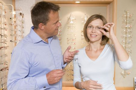 Couple trying on eyeglasses at optometrists smiling Stock Photo - 3485375
