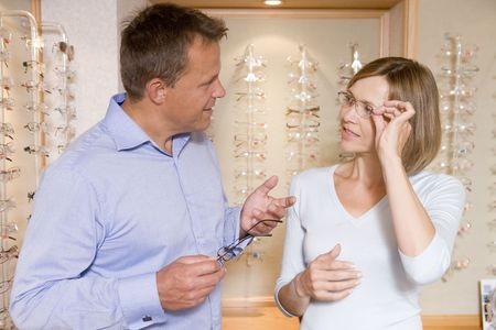 Couple trying on eyeglasses at optometrists photo