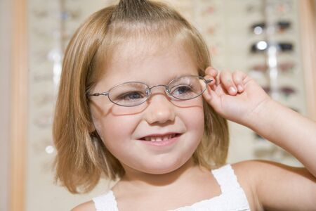 Young girl trying on eyeglasses at optometrists smiling Stock Photo