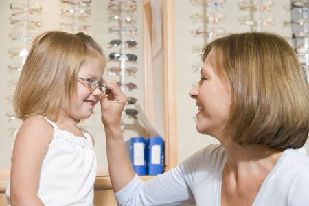 Woman trying eyeglasses on young girl at optometrists smiling photo