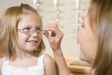 eyeglass frame: Woman trying eyeglasses on young girl at optometrists smiling Stock Photo