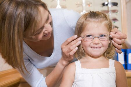 Mujer que trataba de anteojos niña sonriente en optometristas
